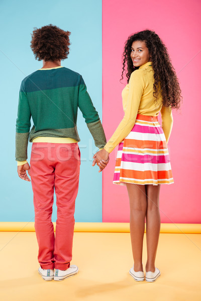 Back view of woman standing and holding hands with boyfriend Stock photo © deandrobot