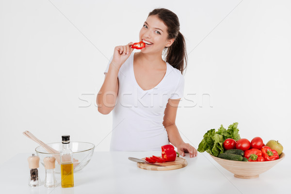 Happy young lady cooking with vegetables while eating them Stock photo © deandrobot