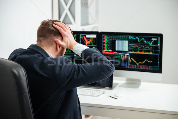 Shocked stressed businessman sitting and holding head by hands Stock photo © deandrobot