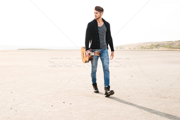 Portrait of a casual man walking across seashore with guitar Stock photo © deandrobot
