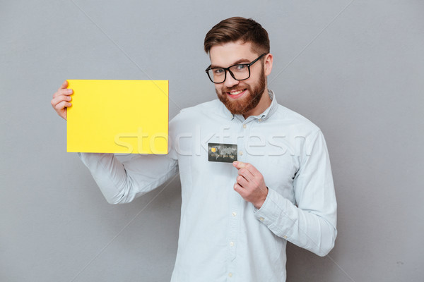 Attractive bearded businessman holding copyspace blank and debit card Stock photo © deandrobot
