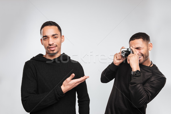 Young african men photographer make a photo of his friend. Stock photo © deandrobot