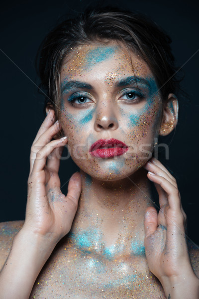 Portrait of beautiful woman with blue sparkles on her face Stock photo © deandrobot