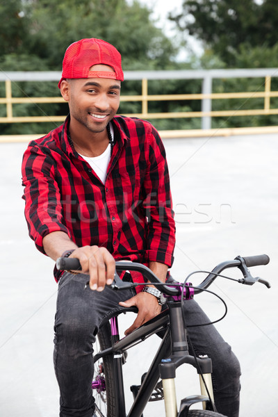 Cheerful dark skinned man wearing cap sitting on his bicycle Stock photo © deandrobot