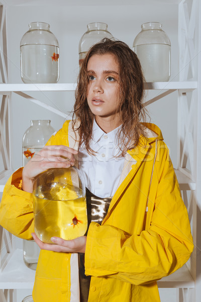 Pensive woman in yellow raincoat holding jar with gold fish Stock photo © deandrobot