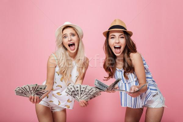 Cheerful emotional women holding money. Stock photo © deandrobot