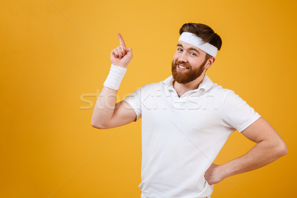 Smiling sportsman holding arm at hip and pointing up Stock photo © deandrobot