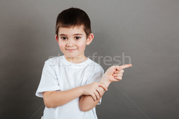 Smiling cute little boy standing and pointing away Stock photo © deandrobot