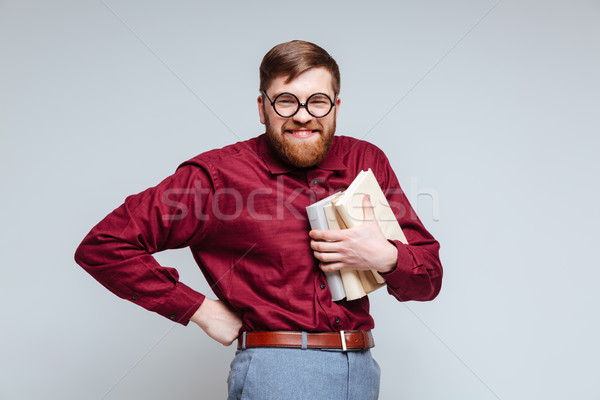 Stock photo: Smiling Male nerd with books