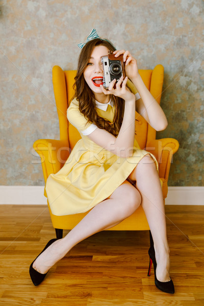 Beautiful happy young pin-up lady with red lipstick holding came Stock photo © deandrobot