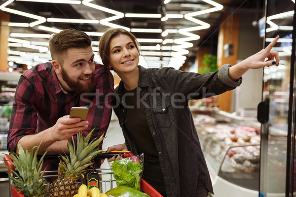 Happy loving couple in supermarket with shopping trolley Stock photo © deandrobot