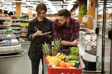 Smiling loving couple in supermarket with shopping trolley Stock photo © deandrobot
