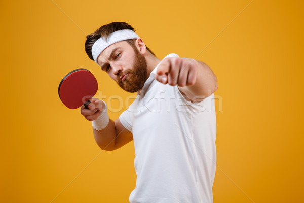 Young sportsman holding racket for table tennis while pointing. Stock photo © deandrobot