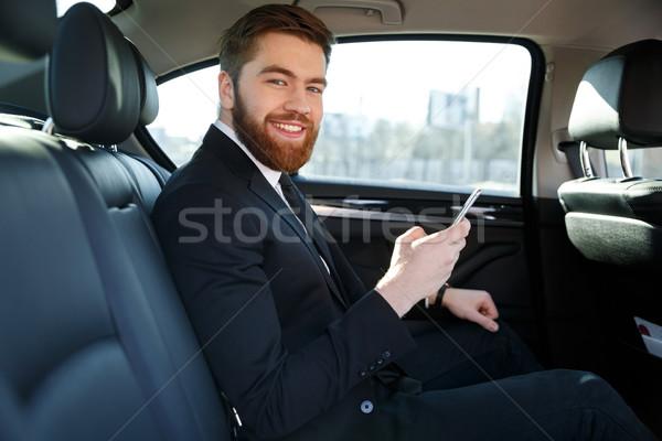 Vista lateral sonriendo barbado hombre de negocios coche sesión Foto stock © deandrobot