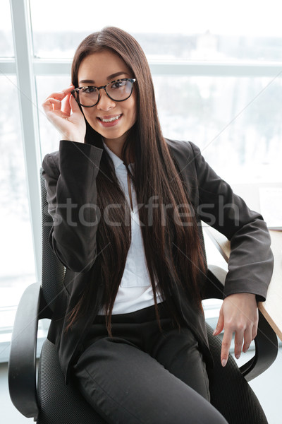 Happy young businesswoman in glasses sitting and smiling at office Stock photo © deandrobot