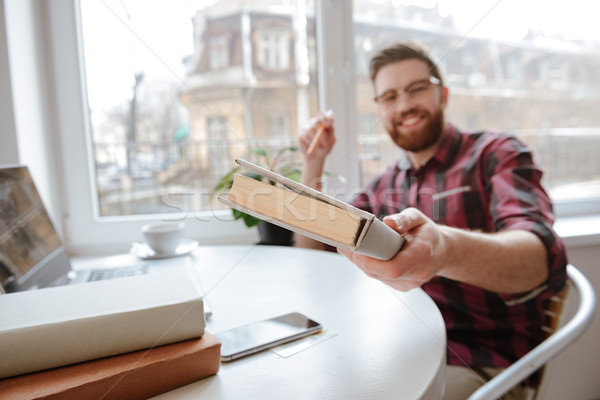 Happy bearded man showing book to camera. Focus on book. Stock photo © deandrobot