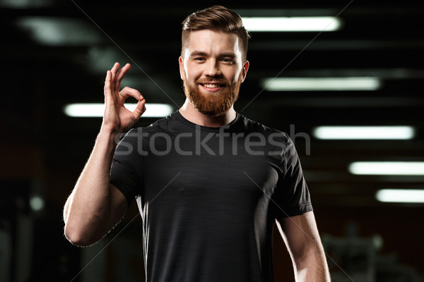 Cheerful sports man posing in gym showing okay gesture. Stock photo © deandrobot