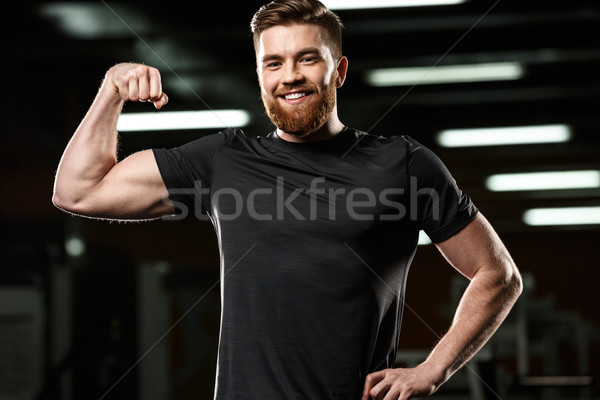 Smiling sports man showing his biceps. Stock photo © deandrobot