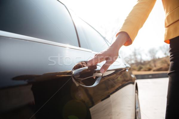 Businesswomen opening the door of black car Stock photo © deandrobot