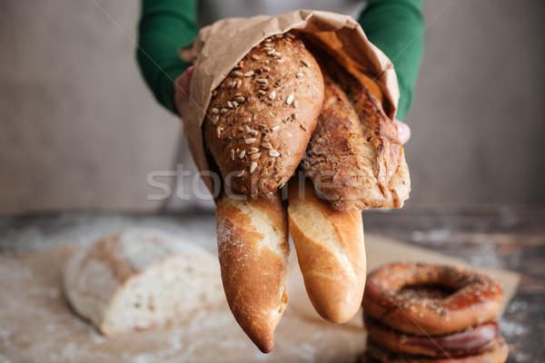 Afbeelding vrouwelijke bakker tonen zak brood Stockfoto © deandrobot