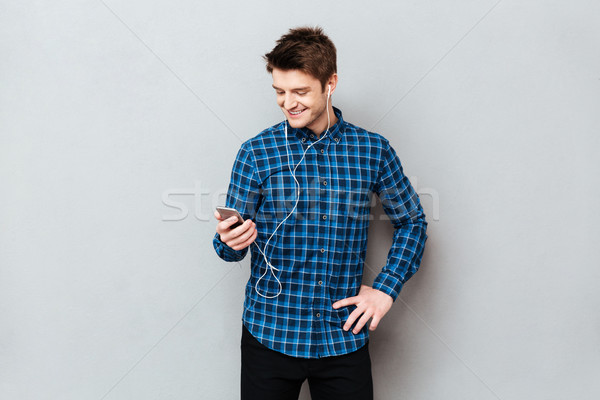 Smiling man using smartphone to choose music Stock photo © deandrobot