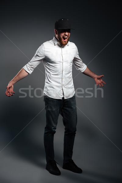 Urlando arrabbiato barbuto giovane indossare cap Foto d'archivio © deandrobot