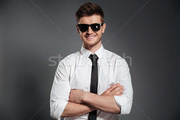 Attractive man in sunglasses and formalwear standing with arms folded Stock photo © deandrobot