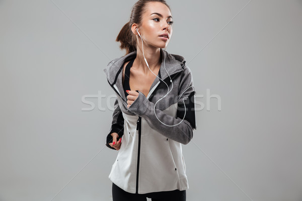 Young female runner in warm clothes running Stock photo © deandrobot