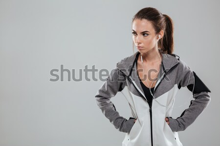 Serious female runner in warm clothes holding hands on hip Stock photo © deandrobot