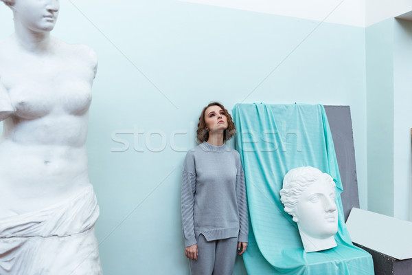 Stock photo: Young woman standing against a wall