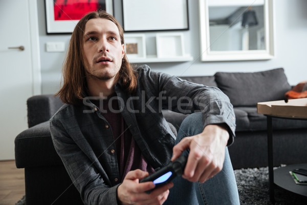 Concentrated man sitting at home indoors play games with joystick Stock photo © deandrobot