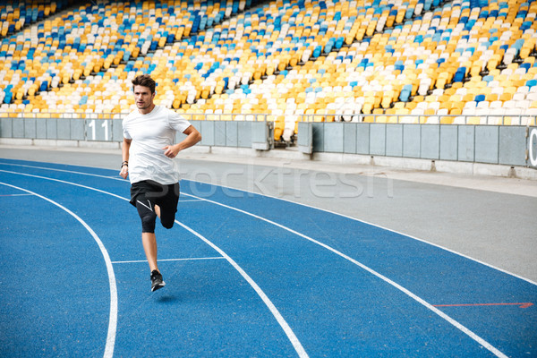 Young sprinter running on athletics track Stock photo © deandrobot