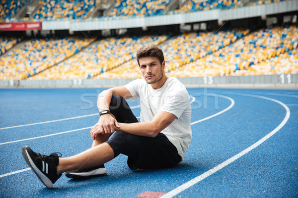 Handsome young sports man sitting at the stadium Stock photo © deandrobot