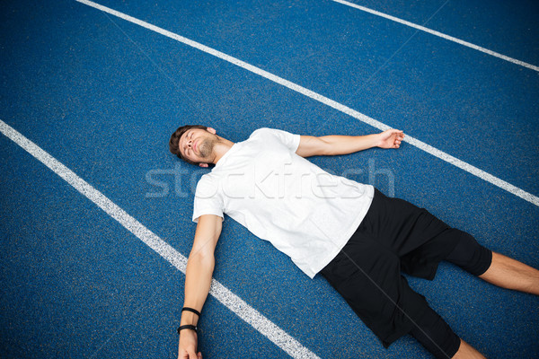 Tired male athlete resting after running while lying on racetrack Stock photo © deandrobot