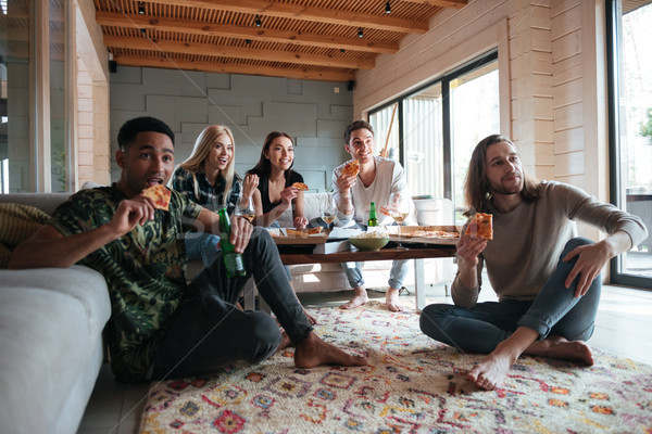 Five friends sitting in house and eating pizza Stock photo © deandrobot