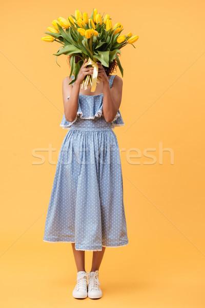 Portré afrikai nő rejtőzködik mögött virágcsokor Stock fotó © deandrobot