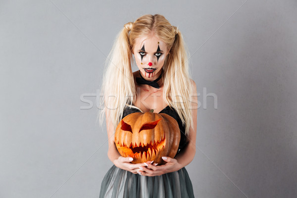 Frightening blonde woman in halloween make up holding carved pumpkin Stock photo © deandrobot