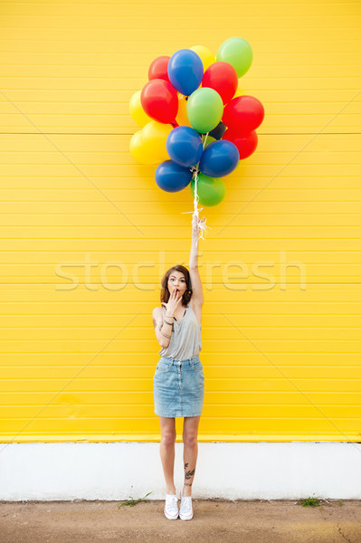 Woman standing over yellow wall. Have fun with balloons. Stock photo © deandrobot
