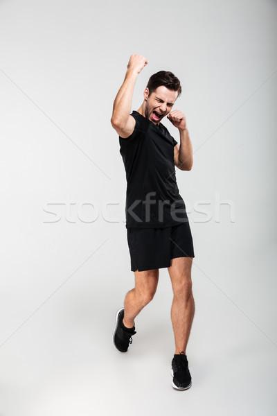 Full length portrait of a pleased happy sportsman Stock photo © deandrobot