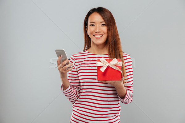 Cheerful young asian woman chatting by phone holding gift. Stock photo © deandrobot
