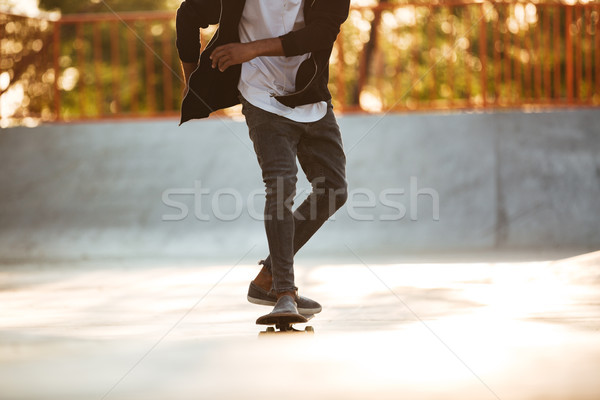 Cropped image of an african skateboarder skating Stock photo © deandrobot