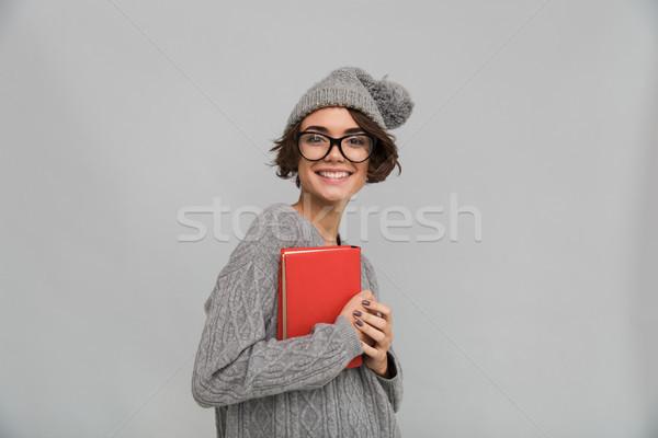 Donna sorridente maglione caldo Hat libro Foto d'archivio © deandrobot
