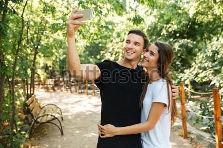 Young happy couple enjoying piggyback ride at the park Stock photo © deandrobot