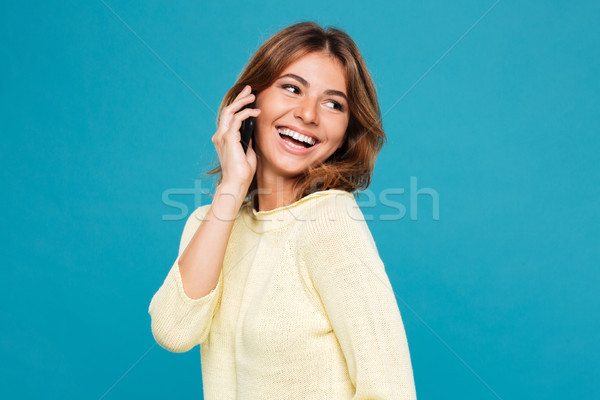 Cheerful woman in sweater talking by smartphone and looking away Stock photo © deandrobot
