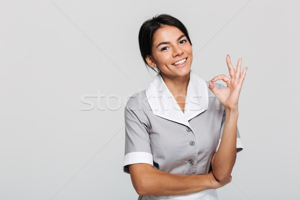 Stock photo: Young attractive maid in uniform showing OK gesture while standi