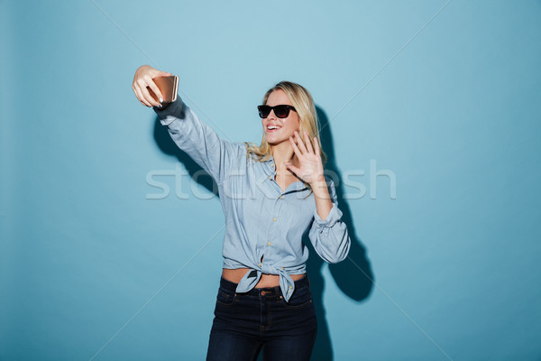 Happy woman in shirt and sunglasses making selfie on smartphone Stock photo © deandrobot