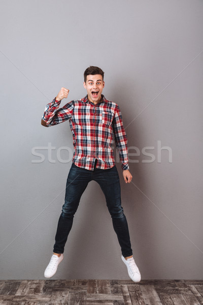 Full-length image of Screaming Cheerful man in shirt and jeans Stock photo © deandrobot