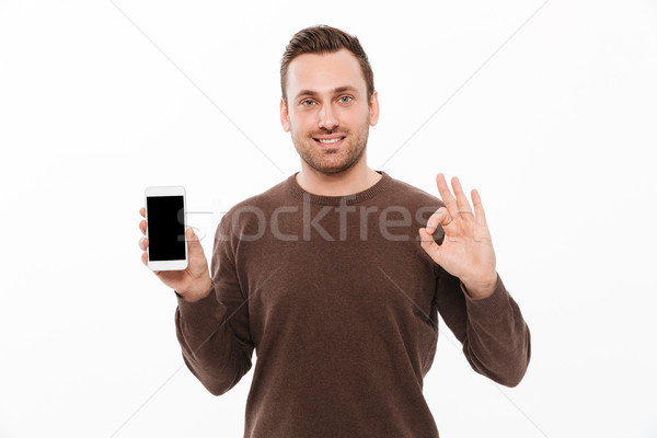 Happy young man showing display of mobile phone Stock photo © deandrobot
