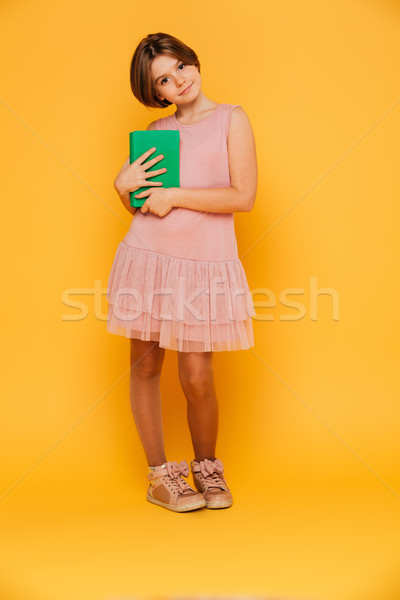 Pretty pensive girl looking camera and holding green book isolated Stock photo © deandrobot