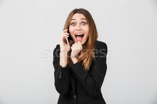 Happy woman talking on smartphone and smiling isolated Stock photo © deandrobot